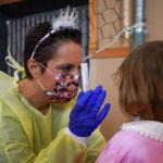 Медик в защитном костюме с элементами новогоднего костюма берет пробу для ПЦР-теста у девочки