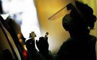Медик в защитной маске и лицевом экране держит пробирки с пробами для анализа на коронавирус