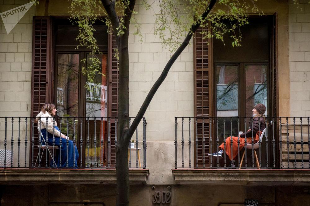 Барселона қаласындағы балконда сөйлесіп отырған әйелдер