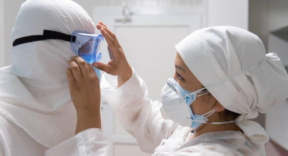 Врач снимает защитный костюм после окончания дежурства в больнице с коронавирусом