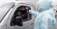 Медик измеряет температуру водителей на блокпосту