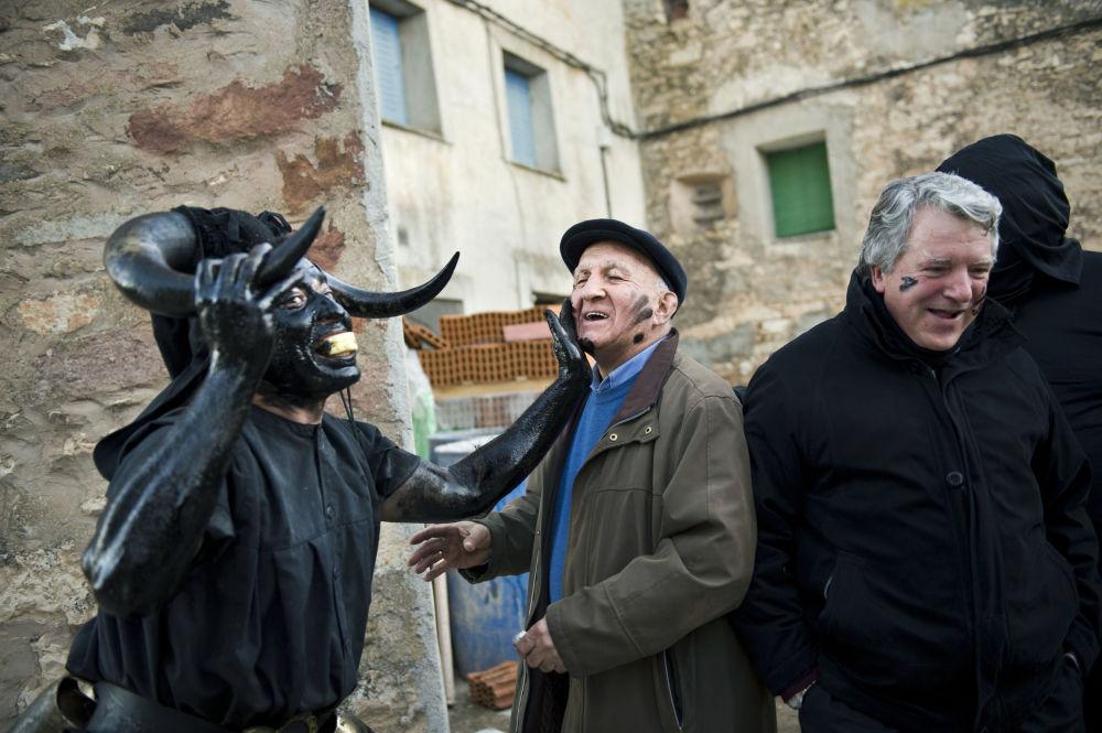 Испанияның Лусон атты шағын ауылындағы карнавал кезінде құбыжық бейнесіндегі адам ауыл тұрғындарының бетіне бояу жағып тұр.