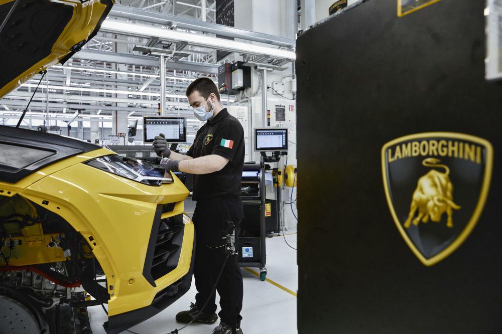 Сант-Агата-Болоньезедегі Lamborghini зауытының монтаждау желісіндегі жұмысшы. Италия.