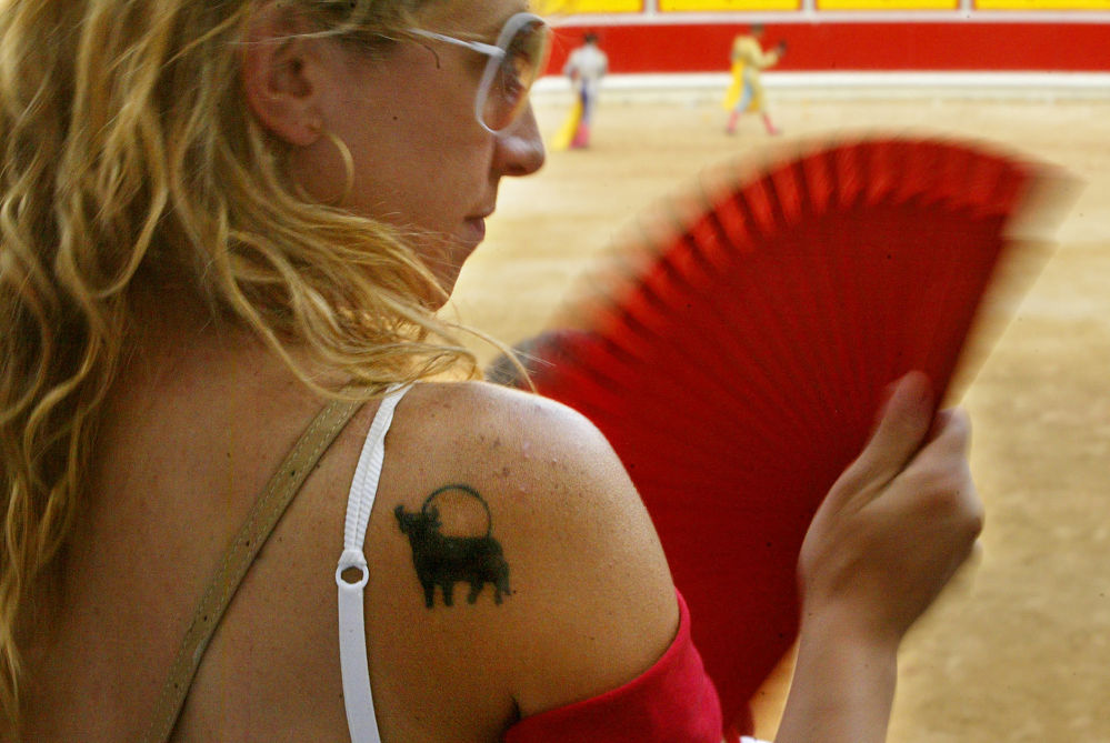 Испанияның Сан-Фермин қаласында өткен коррида жәрмеңкесінде иығында бұқа татуировкасы бар әйел.