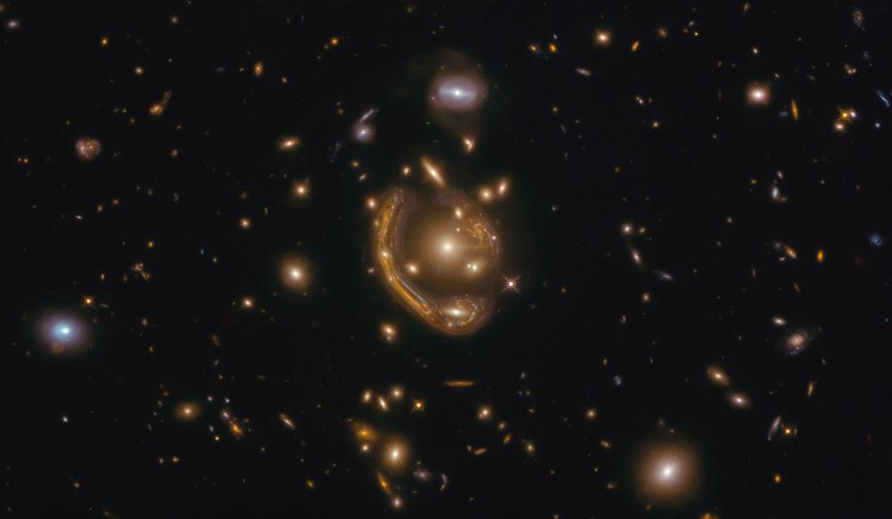 GAL-CLUS-022058 ғарыш галактикасындағы Хаббл ғарыштық телескопы балқытылған сақина сияқты болып көрінеді.