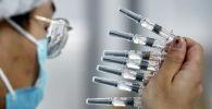 Медик держит несколько шприцев с вакциной от коронавируса
