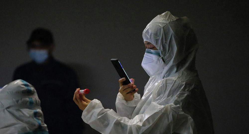 Медик в защитном костюме фотографирует маркированную пробирку с ПЦР-тестом для анализа на коронавирус