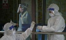 Медики в защитных костюмах проводят ПЦР-тесты на коронавирус