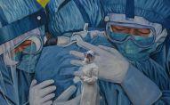 Медик в защитном костюме стоит у стены с муралом, посвященным врачам