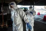 Медработники проводят санитарную обработку защитных костюмов во время смены в госпитале с коронавирусом