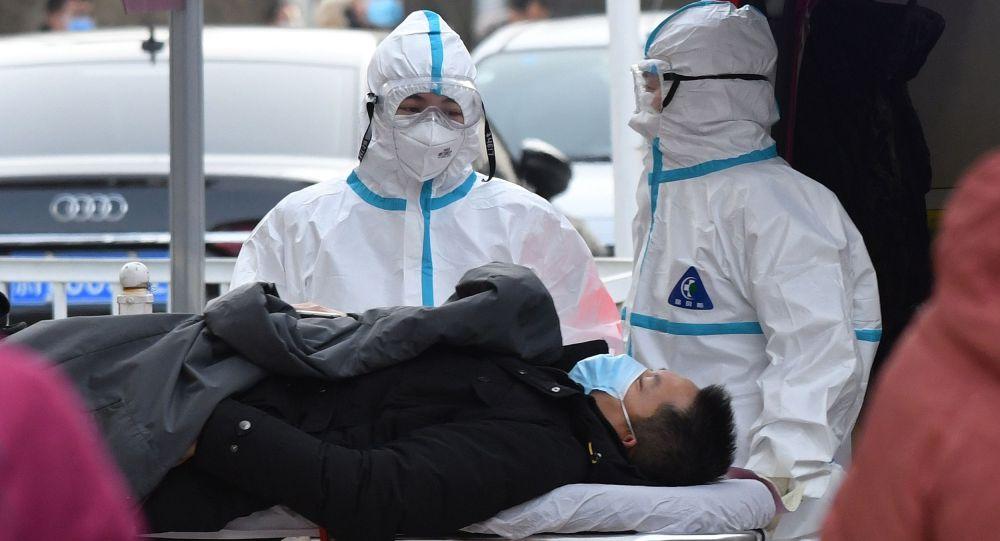 Сотрудники скорой помощи транспортируют пациента с подозрением на коронавирус