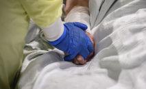Врач держит за руку пожилого пациента палаты интенсивной терапии в больнице с коронавирусом