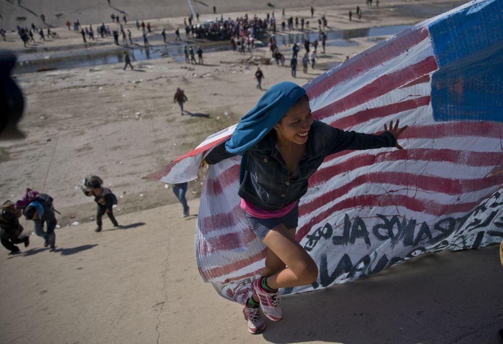 Мигрант әйел Мексикамен шекарада АҚШ-тың қолдан жасаған туын алып жүруге көмектесуде.