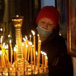 Женщина ставит свечи в церкви в Крещение