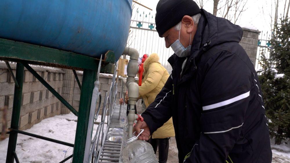 Люди набирают освященную в Крещение воду из емкостей у церкви