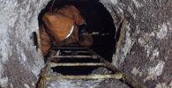 Коммунальщик спускается в канализационный люк