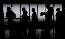 Люди в защитных костюмах стоят в очереди на регистрацию в аэропорту