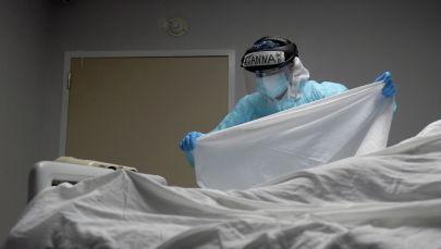 Медик в защитном костюме накрывает тело погибшего от коронавируса пациента