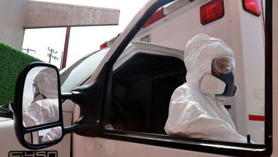 Водитель скорой помощи в защитном костюме стоит возле машины