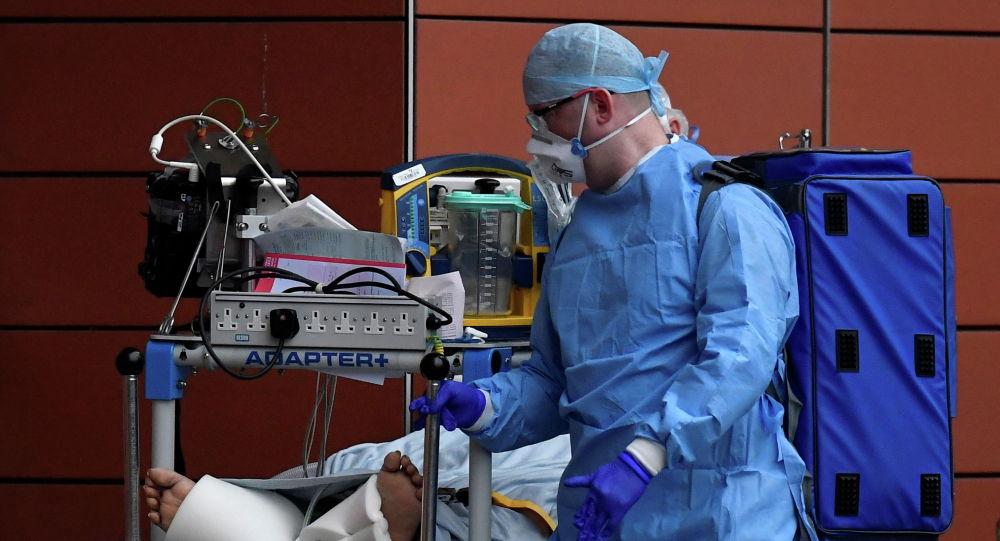 Медик в защитном костюме транспортирует пациента с коронавирусом в больницу