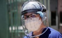 Медик в защитном костюме у больницы с коронавирусом
