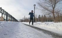Человек бежит по зимней набережной