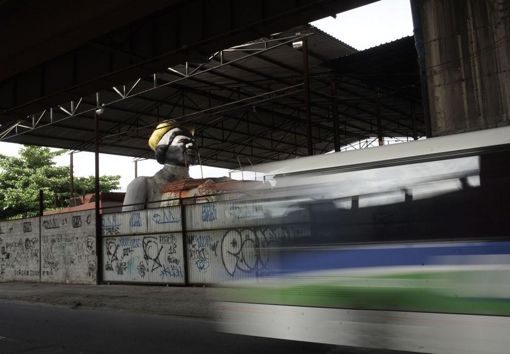 Карнавал шеруі үшін әзірленген мүсін Рио-де-Жанейродағы шеберхананың төбесінен қарап тұр.