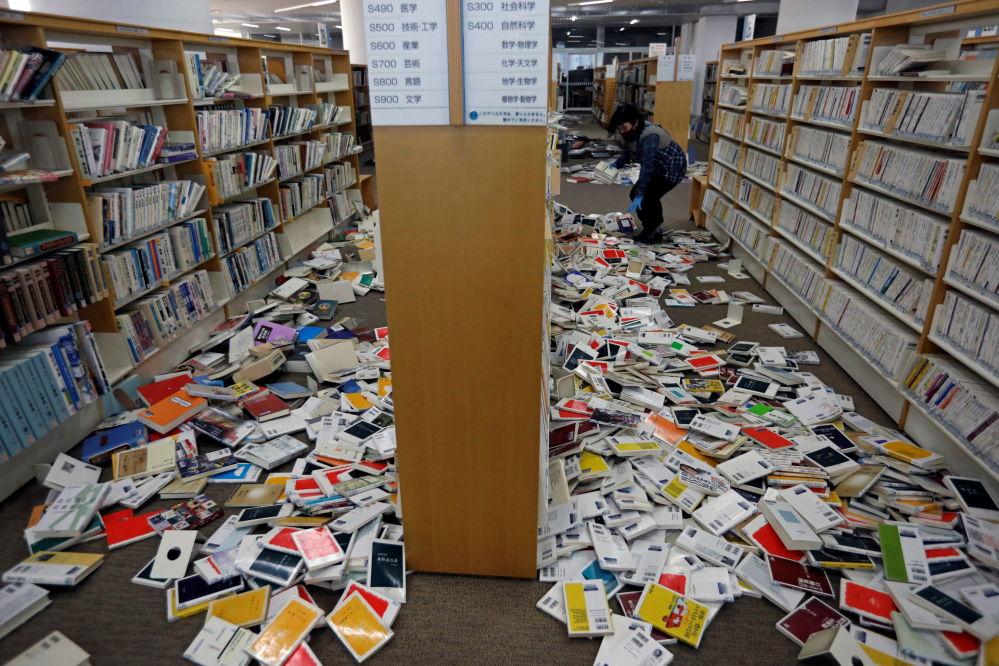 Иваки қаласындағы кітапхана қызметкері жер дүмпуінен шашылып қалған кітаптарды жинастыруда.
