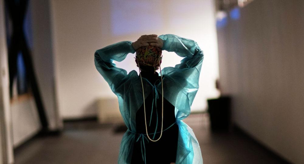 Медсестра в защитном костюме идет по коридору больницы с коронавирусом