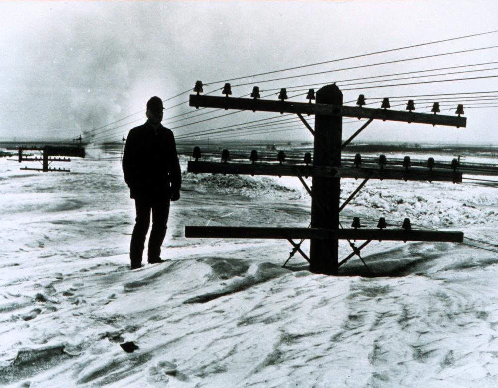 Солтүстік Дакотада ақ түтек бораннан кейін қар басып тұрған ер адам, 1966 жыл.