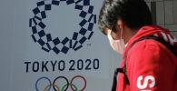 Человек в маске проходит мимо плаката с символикой Олимпиады в Токио