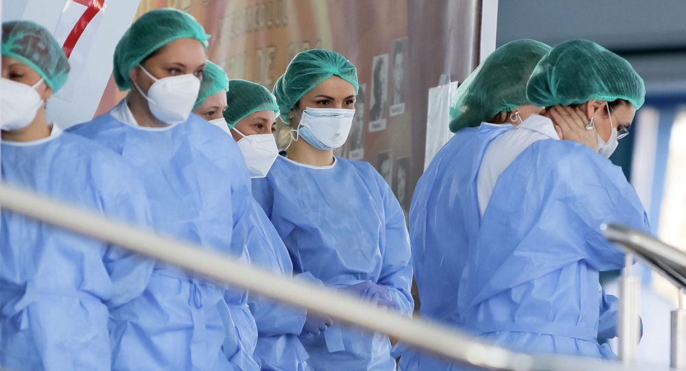 Медики в защитных костюмах ожидают начала смены в центре тестирования
