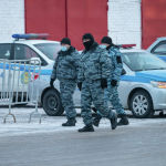 Полицейские в масках идут мимо припаркованных автомашин