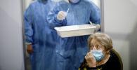Пожилая женщина в пункте вакцинации от коронавируса