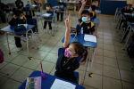 Девочка в защитной маске поднимает руку для ответа на уроке в классе