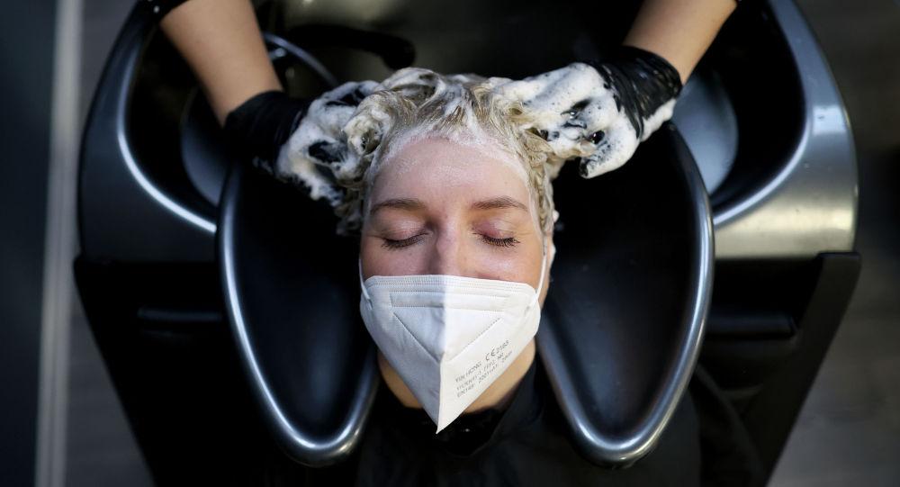 Женщина в маске у парикмахера в салоне