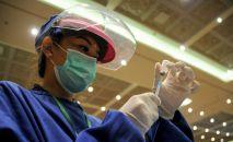 Медработник в защитном костюме набирает вакцину от коронавируса в шприц