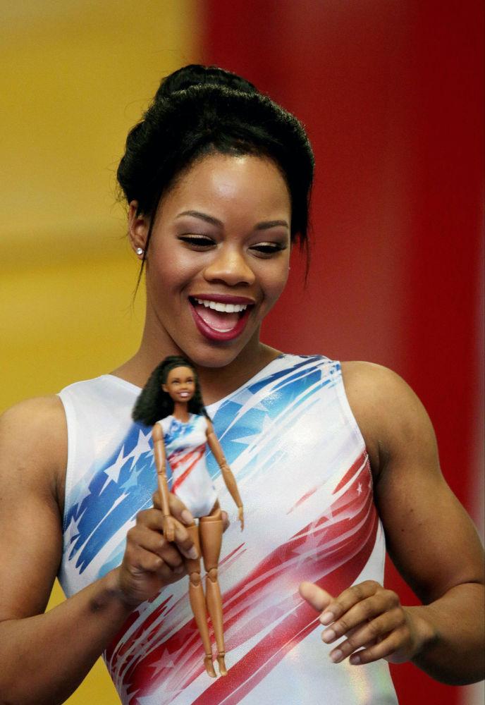 Олимпиада чемпионы, қара нәсілді америкалық гимнастшы Габби Дуглас Barbie қуыршағымен бірге