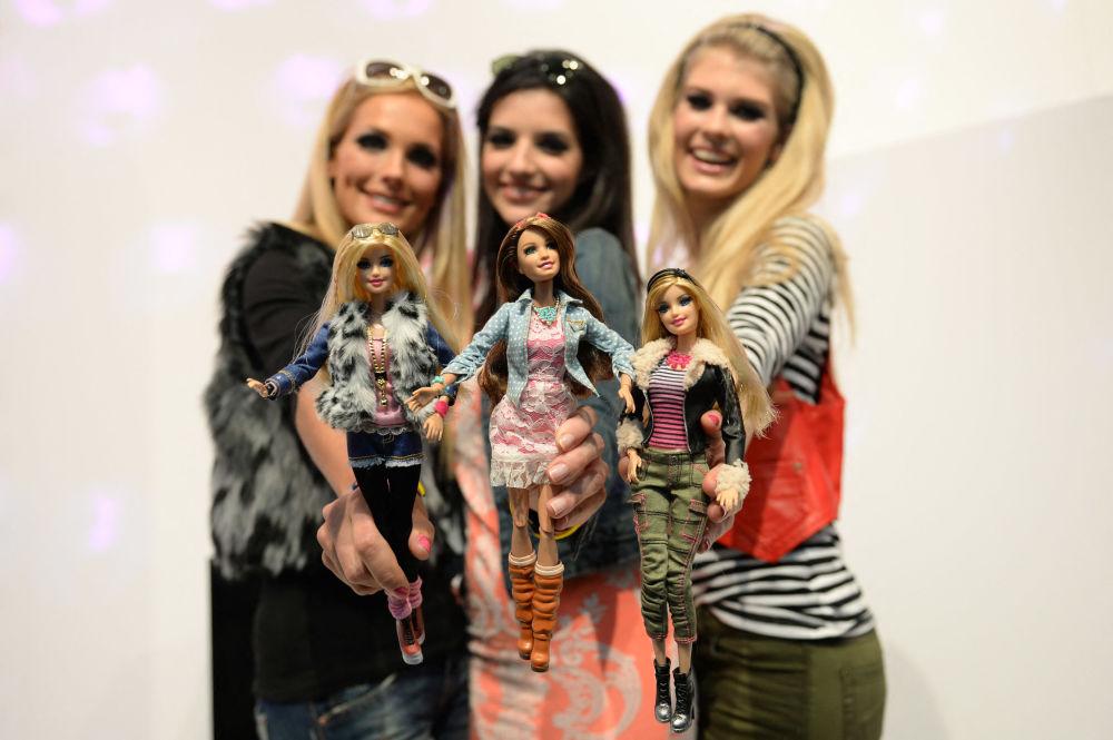 Сәнқойлар 2014 жылы Нюрнбергте өткен ойыншықтар көрмесінде өздеріне ұқсас киім киген Barbie қуыршақтарымен бірге суретке түсіп тұр.