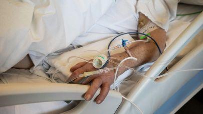 Рука пациента с капельницами в палате интенсивной терапии в больнице с коронавирусом