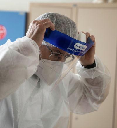 Врач поправляет защитный лицевой щиток перед началом смены в больнице с коронавирусом