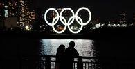 Люди в масках стоят на набережной на фоне гигантских светящихся олимпийских колец в Токио