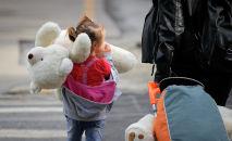 Девочка гуляет с большим плюшевым медведем рядом с мамой