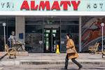 Женщина проходит мимо входной группы отеля Алматы