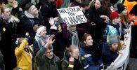 Экоактивист Грета Тунберг держит плакат с надписью школьная забастовка за климат (на шведском языке Skolstrejk för klimatet)
