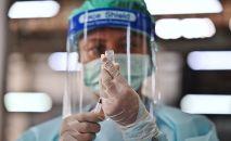 Медик в защитном костюме набирает в шприц вакцину от коронавируса