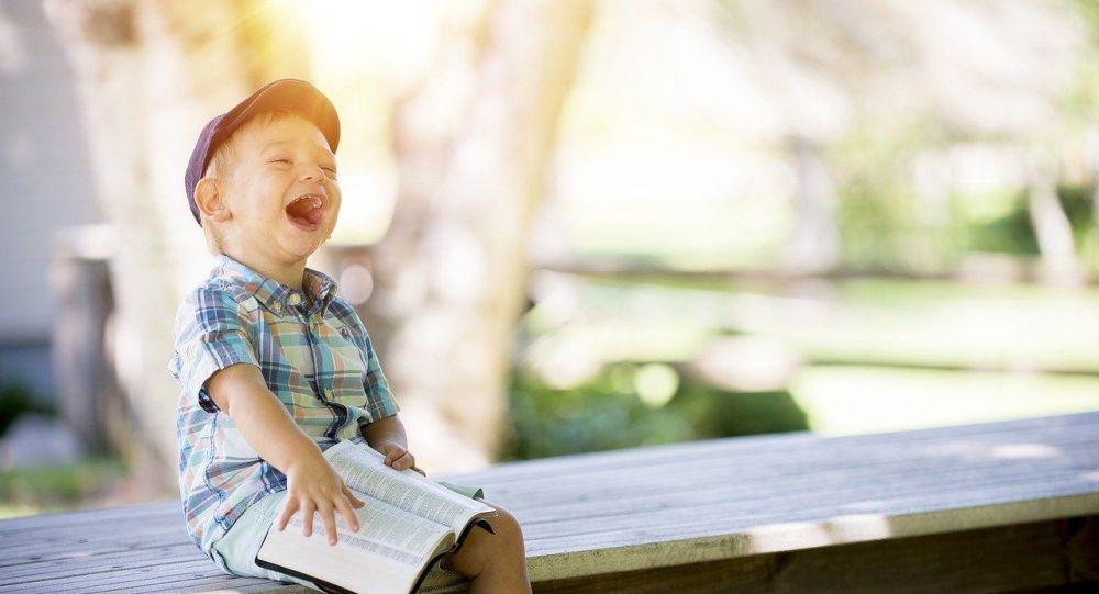 Смеющийся мальчик читает книгу