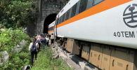 Люди идут рядом с поездом, который сошел с рельсов в туннеле к северу от Хуаляня, Тайвань, 2 апреля 2021 года