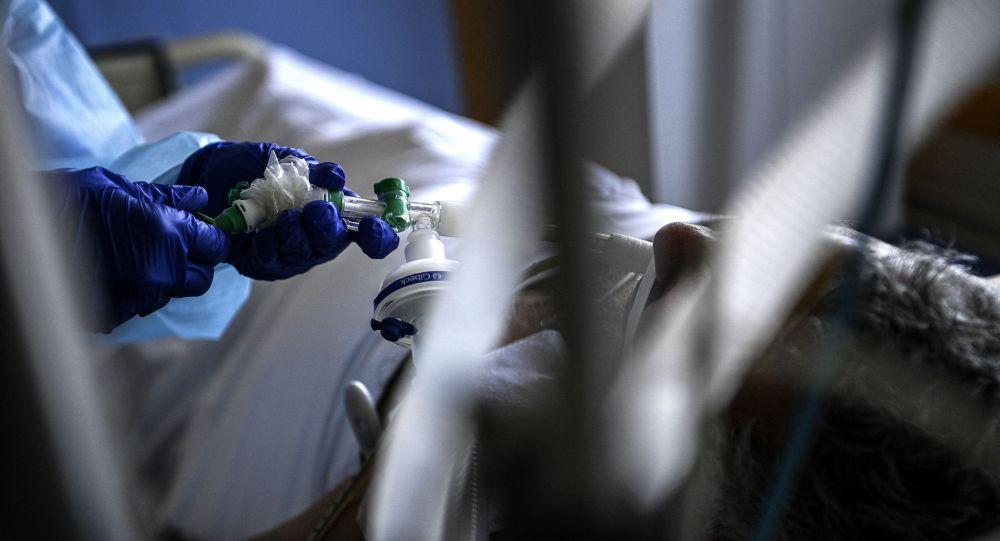 Медик подключает пациента в палате интенсивной терапии к аппарату искусственной вентиляции легких в больнице с коронавирусом
