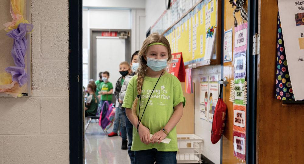 Дети в масках выходят с урока в школе после ослабления карантина